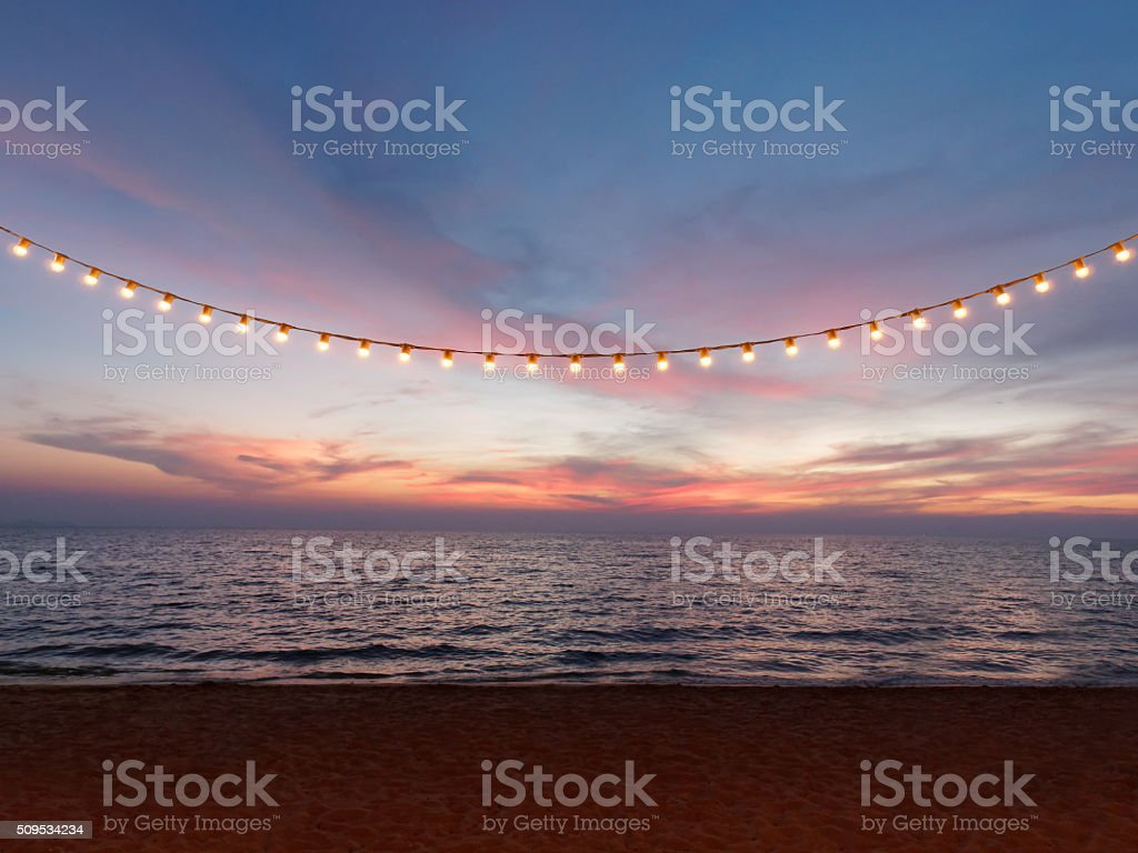light bulbs on string wire against sunset sky stock photo