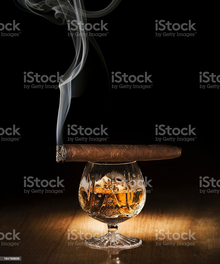 A light cigar on top of a glass of cognac royalty-free stock photo