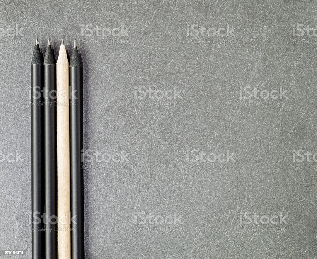 Light Colored Pencil Among Three Black Ones stock photo