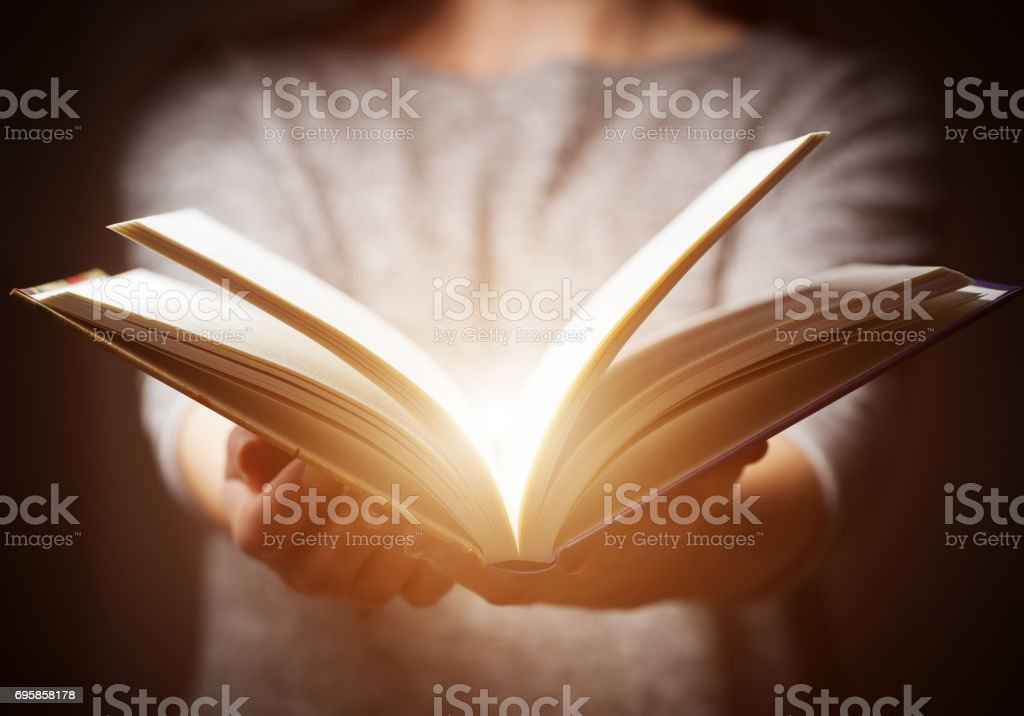Light coming from book in woman's hands in gesture of giving,...