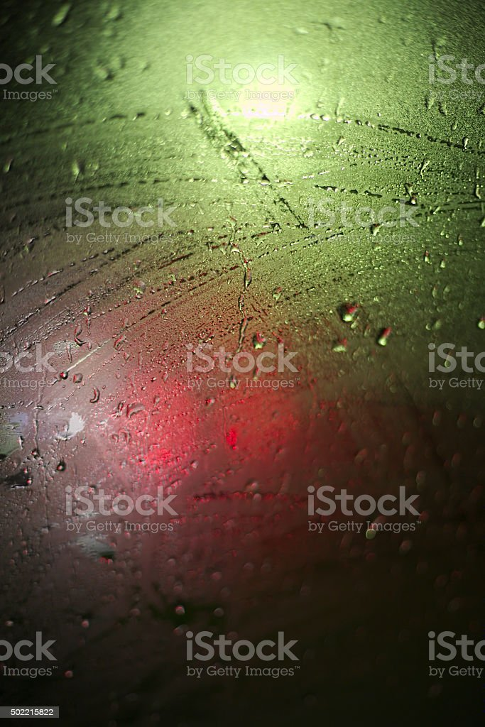 Light effects on a wet glass pane with water drops stock photo