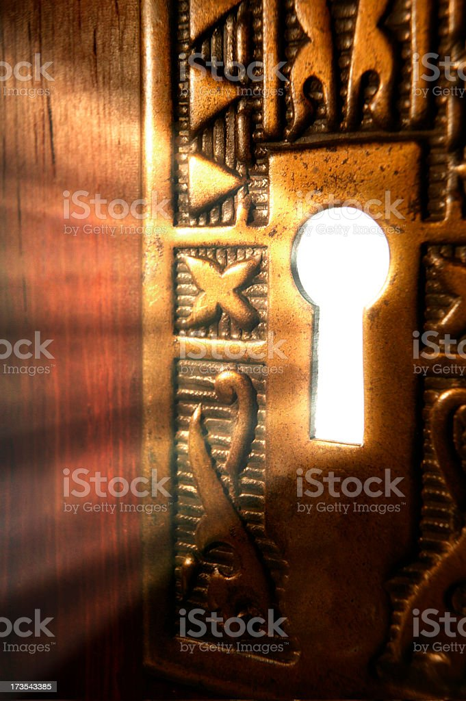 Light emanating through a key hole from a mysterious room stock photo