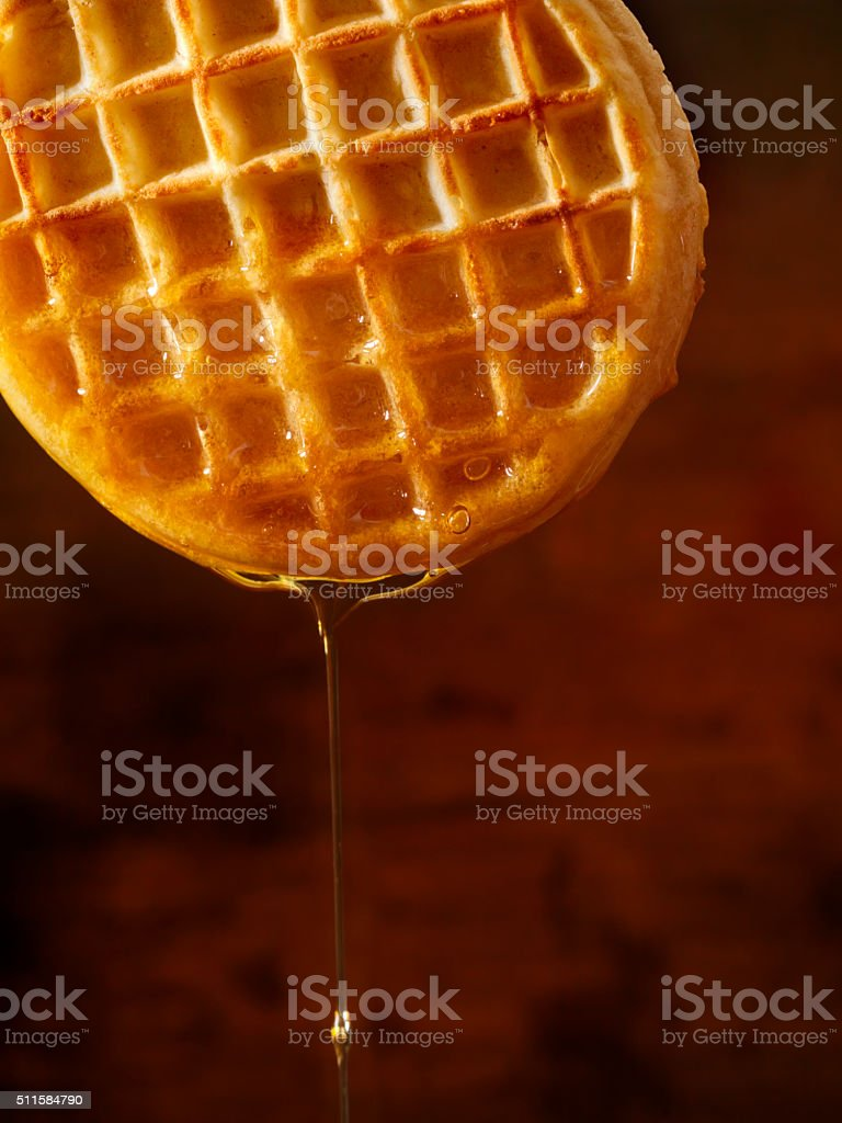 Light Flaky Waffles with Dripping Maple Syrup stock photo