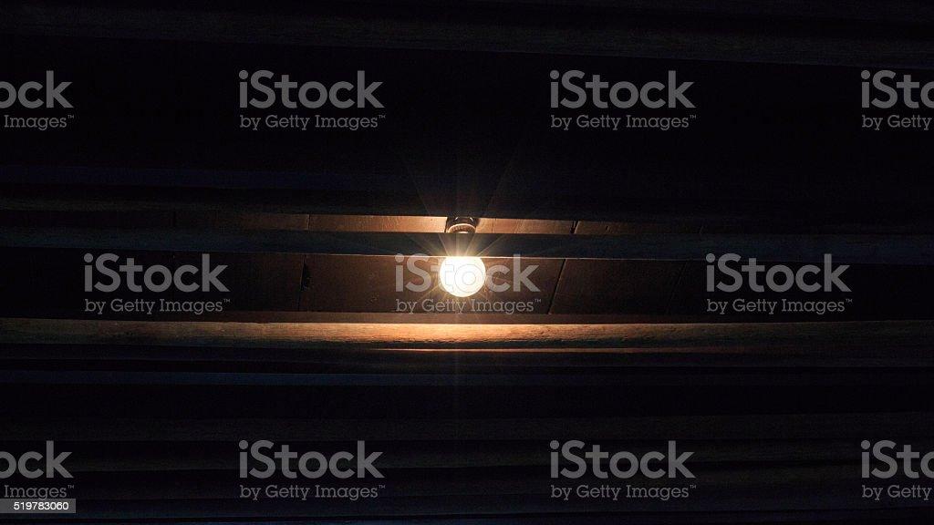 Освещение с лампочку над темный старый деревянный фон Стоковые фото Стоковая фотография