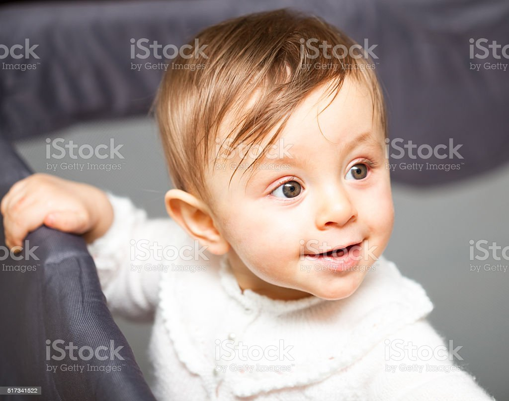 Light haired green eyed baby girl in play pen stock photo