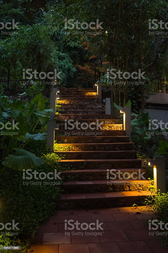 Light on stairs at dusk in garden. stock photo