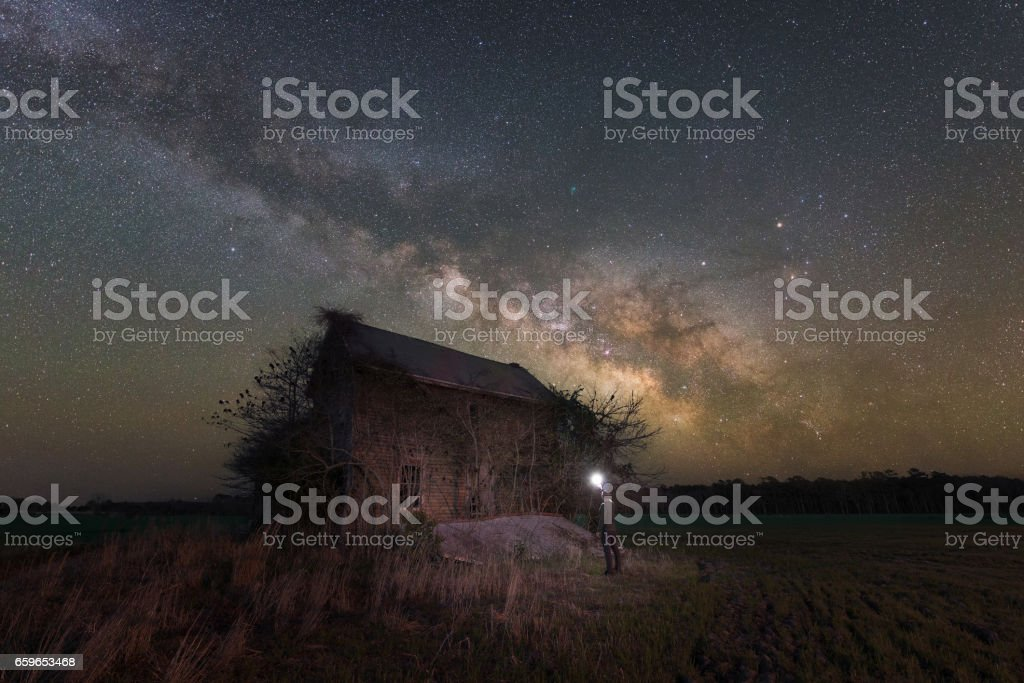 Milky way galaxy rising behind a old farm home.