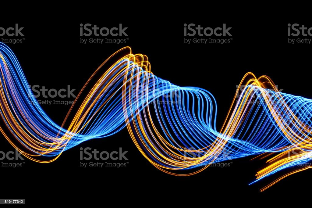 A long exposure photo of blue and gold fairy lights in a swirly...