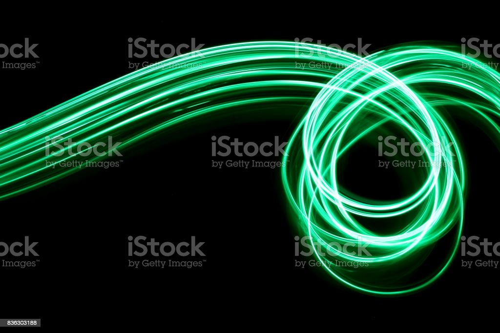A long exposure photo of green fairy lights in a swirly pattern,...