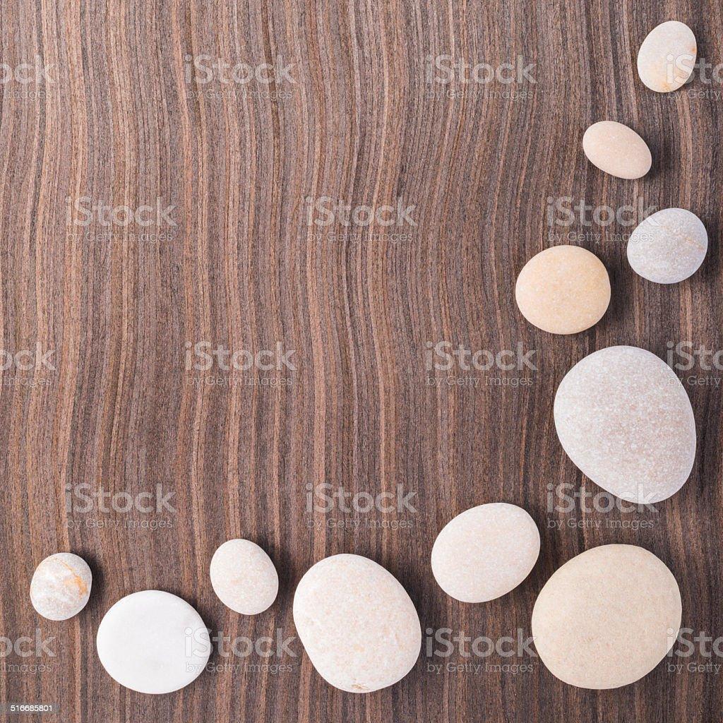 light pebbles on wooden ebony tree background stock photo