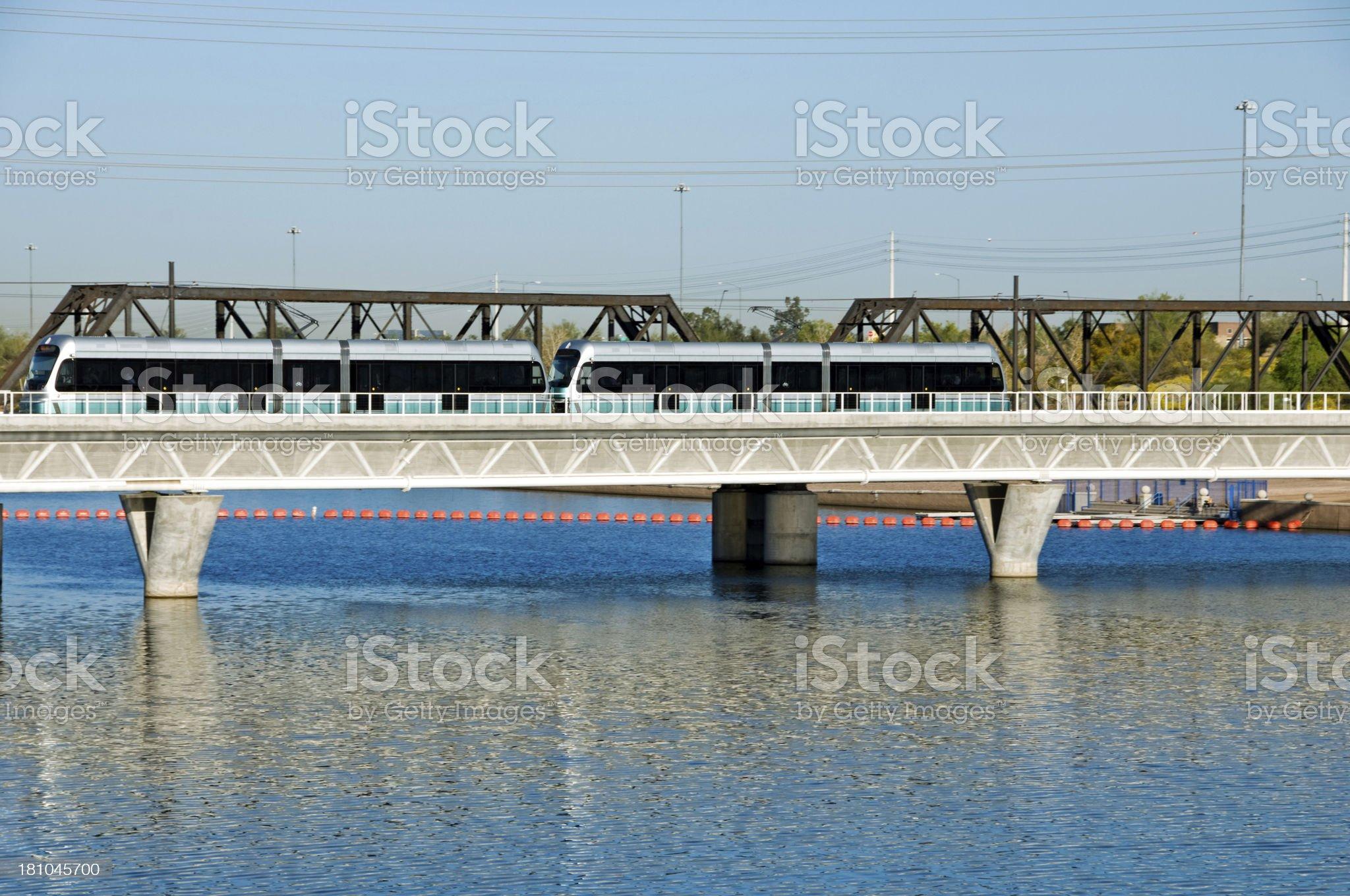 Light rail train crossing man-made lake in Tempe AZ royalty-free stock photo