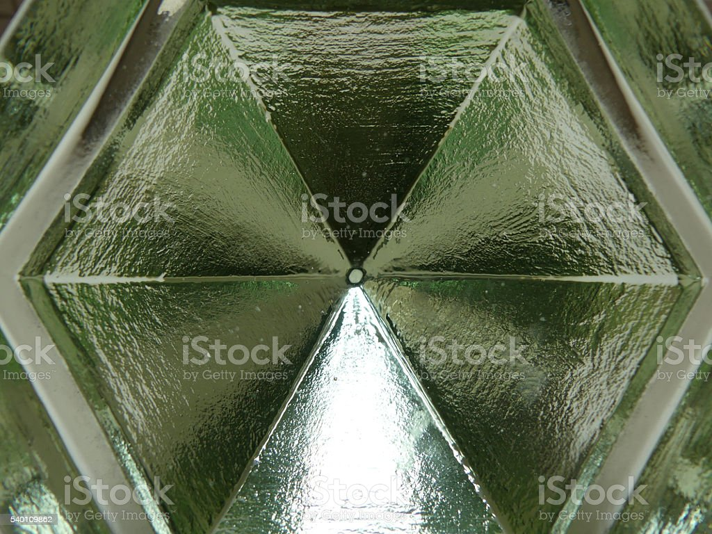 Light refracted through green glass prism stock photo