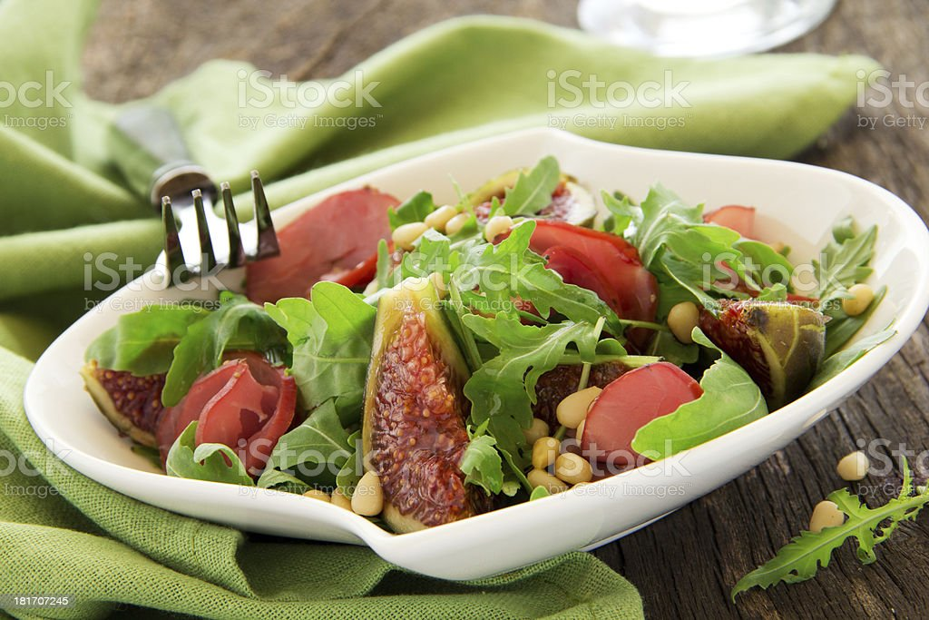 Light salad with figs, bacon, arugula and pine nuts. royalty-free stock photo