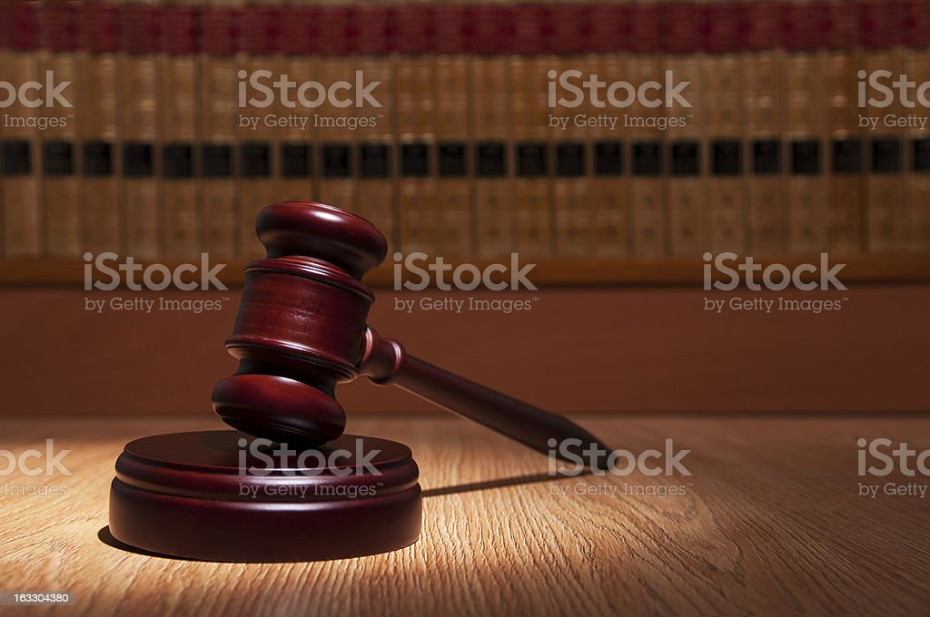 Light shining on judge gavel with background of legal books royalty-free stock photo