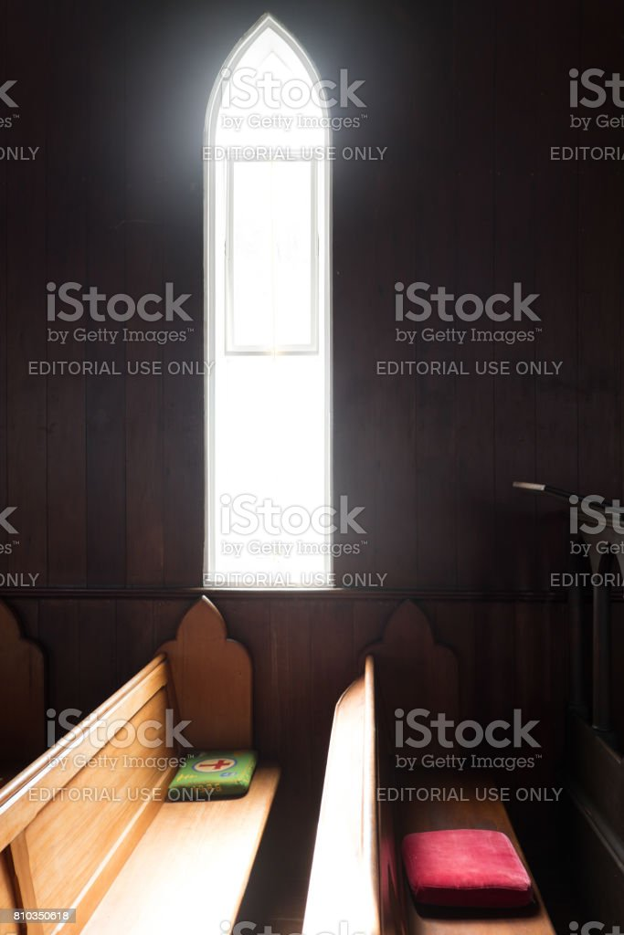 Light shining through church window onto wooden pews at St John The Baptist Anglican Church stock photo