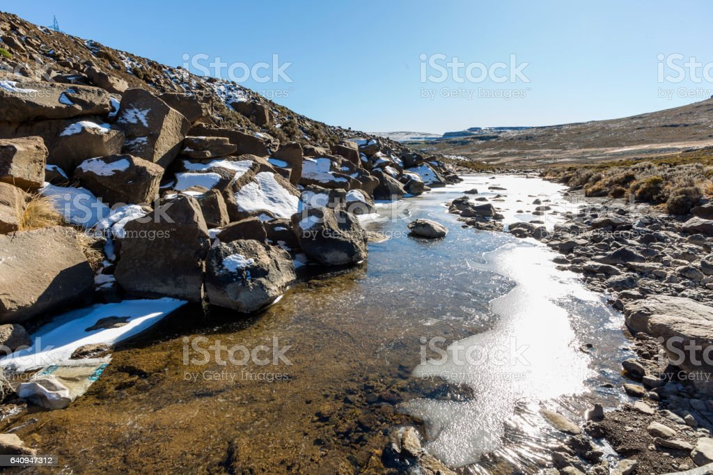 Light snow and frozen stream stock photo