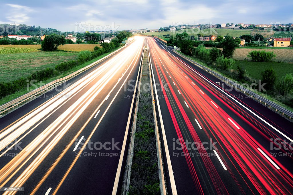 Light Trails Crossing an Hilly Landscape, Marches, Italy stock photo