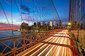 Light trails on Brooklyn Bridge against skyline