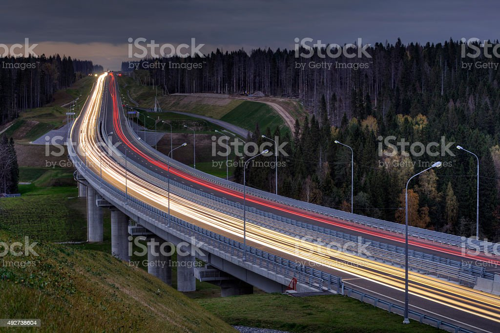 Light trails on four lane highway, crosses the night forest. stock photo