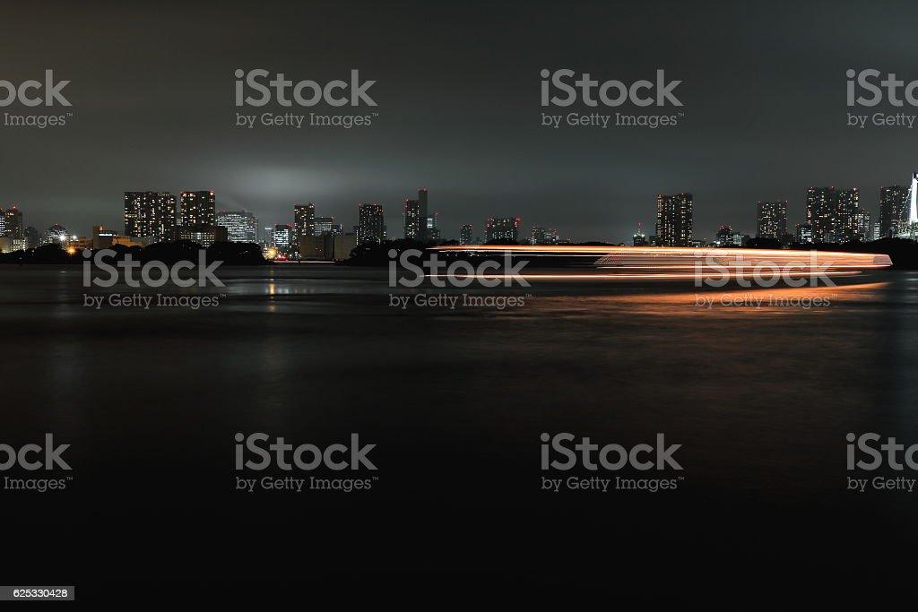 Light trails-ship under Rainbow Bridge crossing northern bay. Tokyo-Japan. 8020 stock photo