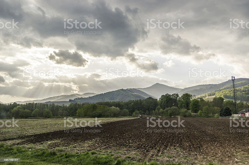 Light-beams over cultivated field stock photo