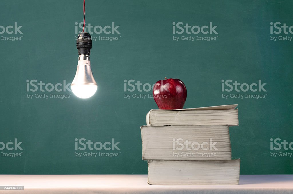 Lightbulb and apple on book stock photo