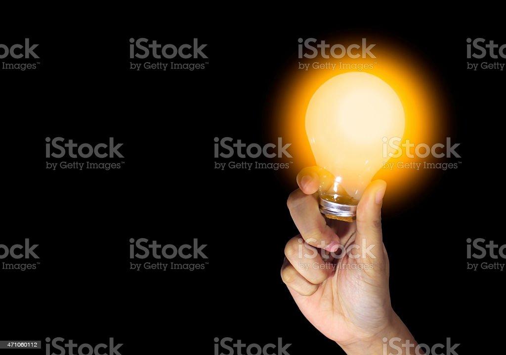 lightbulb held in hand on black background stock photo