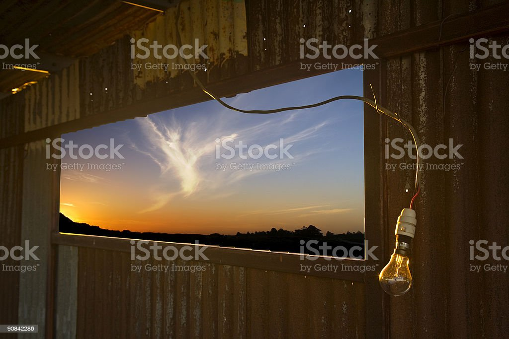 Lightbulb in Galvanised Iron Shed with Last Rays of Sun royalty-free stock photo