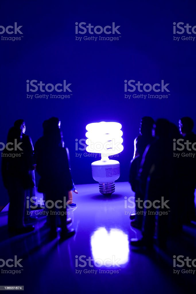 Lightbulb of the future. Compact fluorescent bulb. People in silhouette. royalty-free stock photo