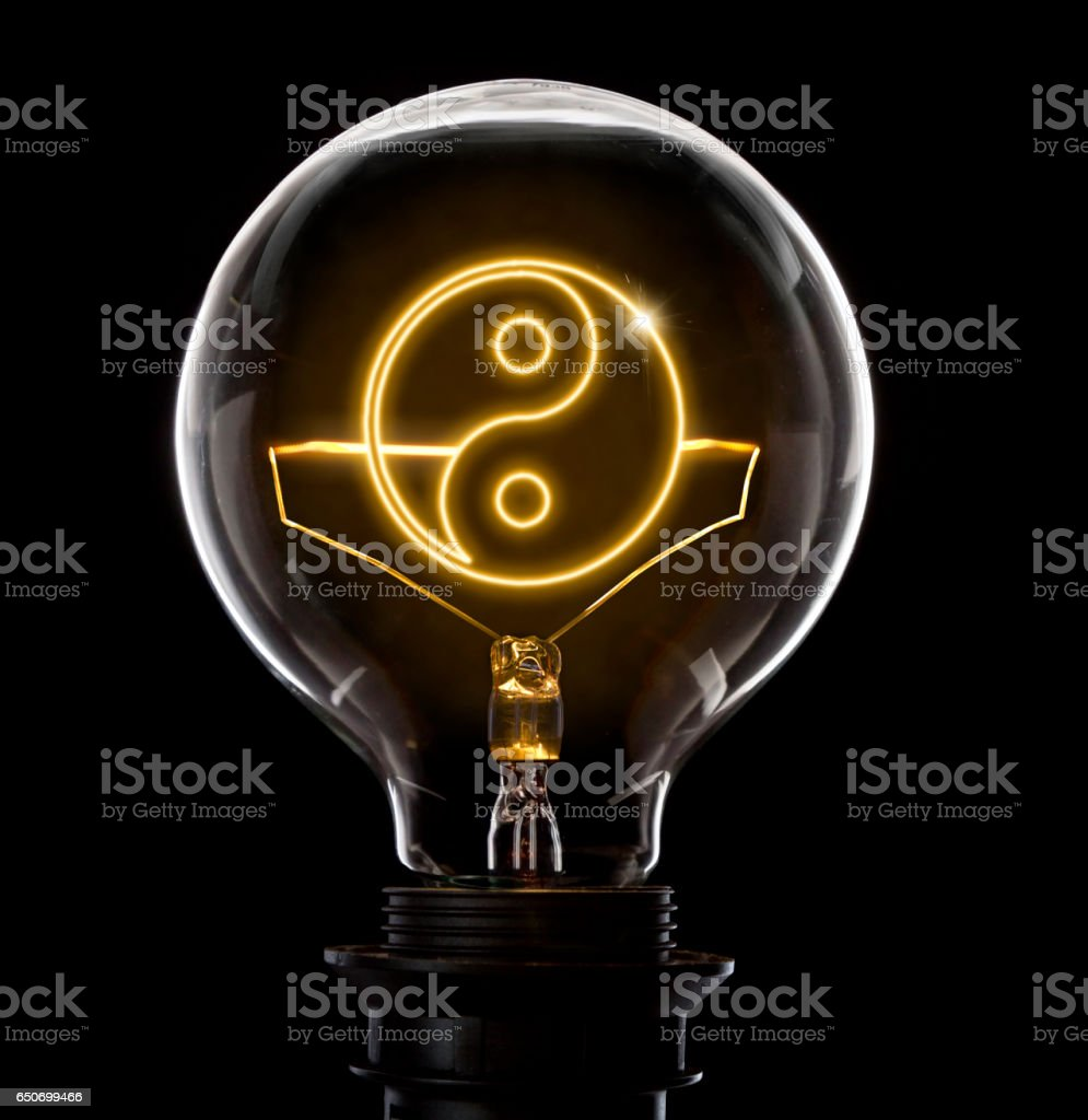 Lightbulb with a glowing wire in the shape of a Ying Yang symbol (series) stock photo