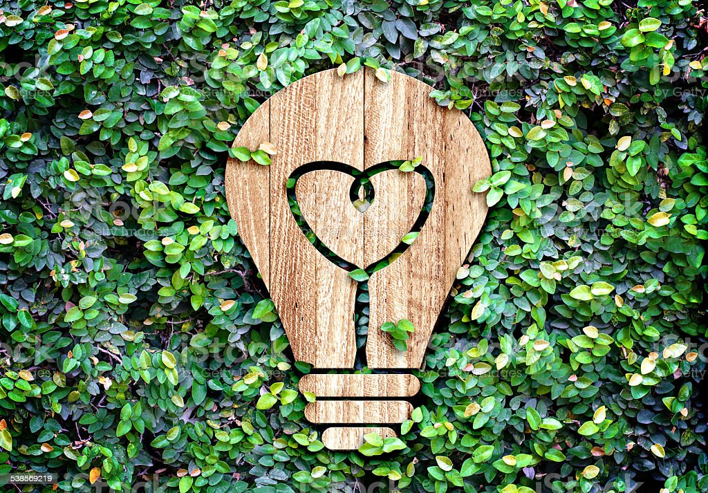 LightBulb wood icon and heart inside on green leaf wall stock photo