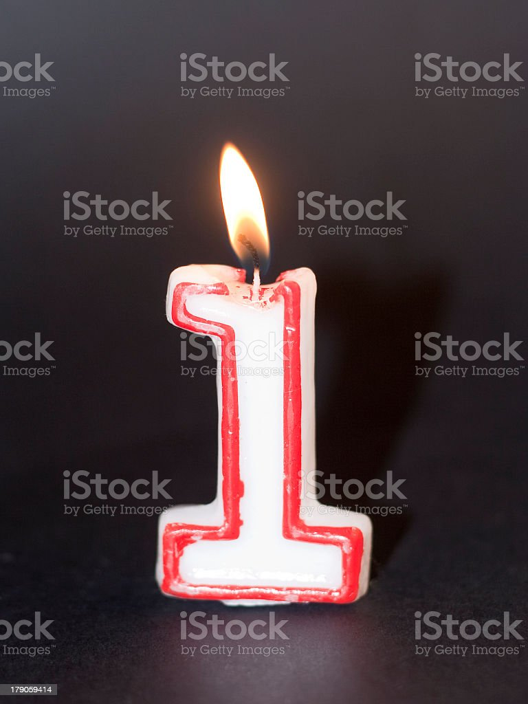 A lighted birthday number one candle stock photo