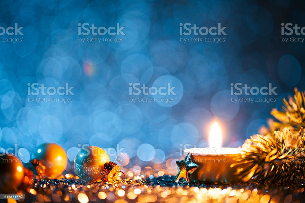 Lighted candle and christmas decorations on defocused blue background stock photo