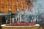 Lighted candle and incense for Buddha. Selective focus.