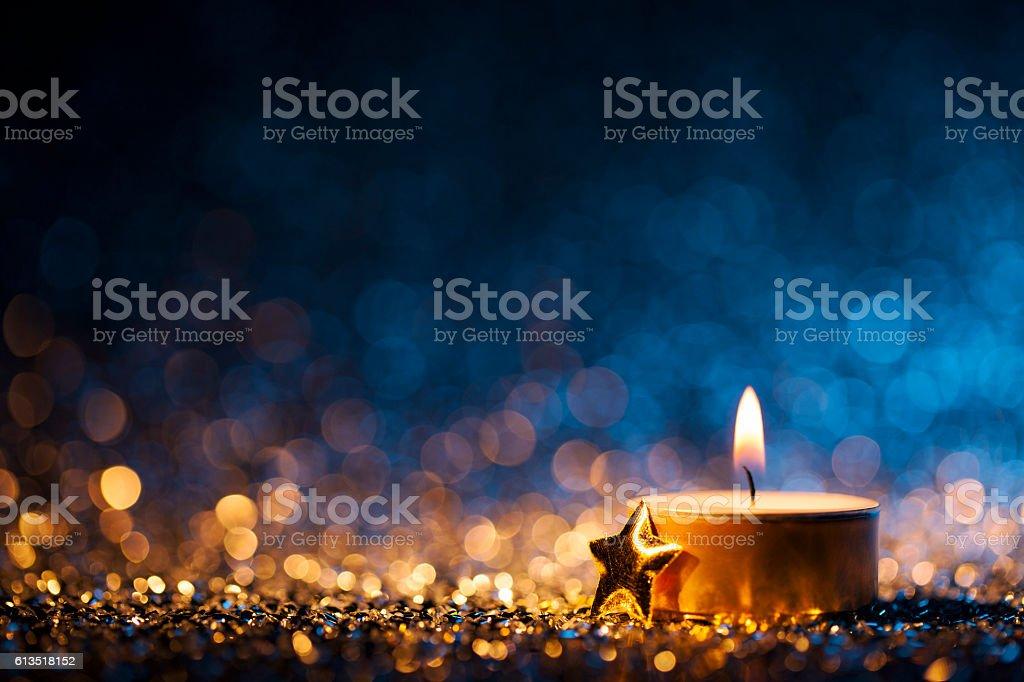 Lighted candle on defocused blue background - Christmas Tea Light stock photo