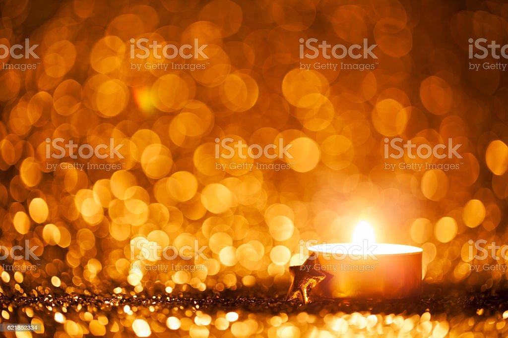 Lighted candle on defocused lights - Background Christmas Tea Light stock photo