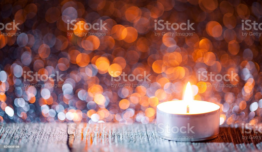 Lighted candle on defocused lights - Background Christmas Tea Light stock photo