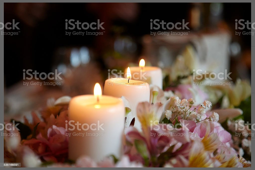 Lighted candles and flowers in a wedding centerpiece stock photo