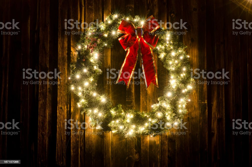 Lighted Christmas Wreath on Old Barn stock photo
