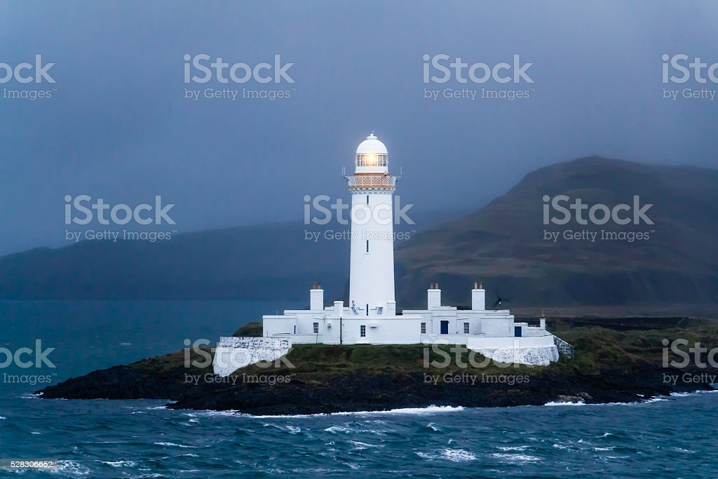 Lighted Lismore lighthouse in Scotland at dusk stock photo