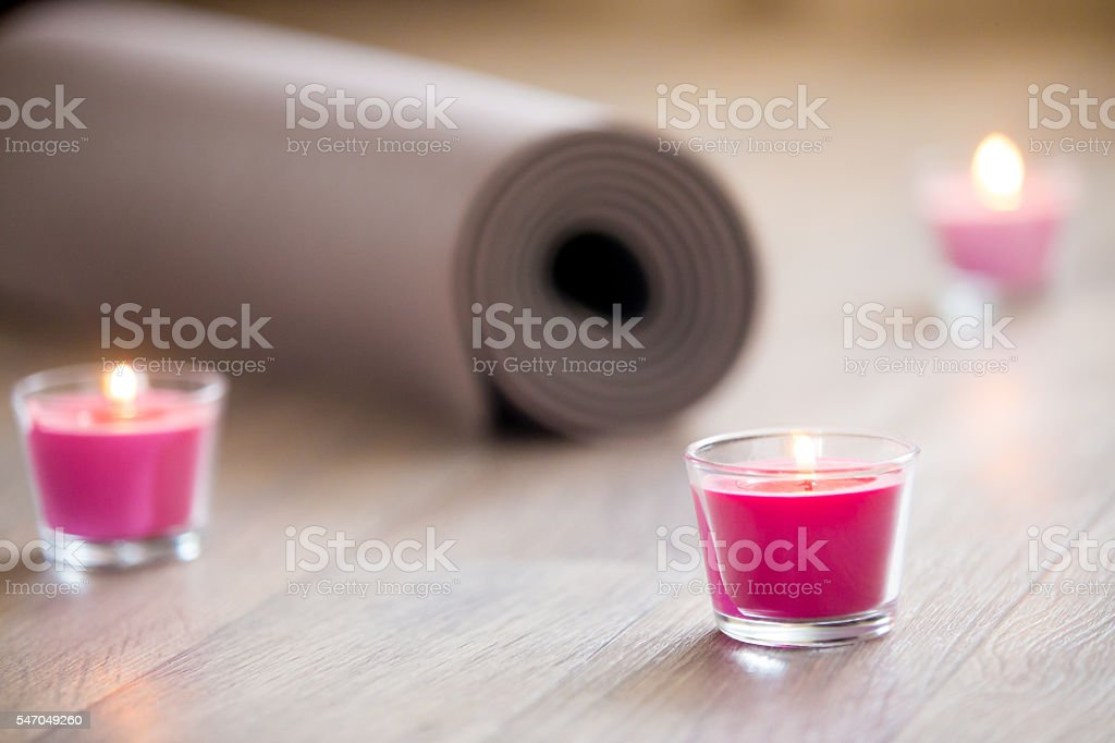 Lighted pink candle and rolled brown yoga, pilates mat stock photo