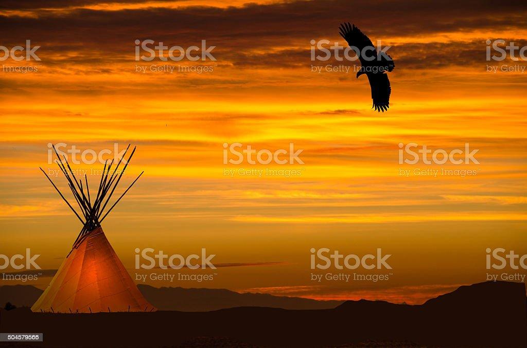 Lighted  teepee and eagle overhead- orange sunset stock photo
