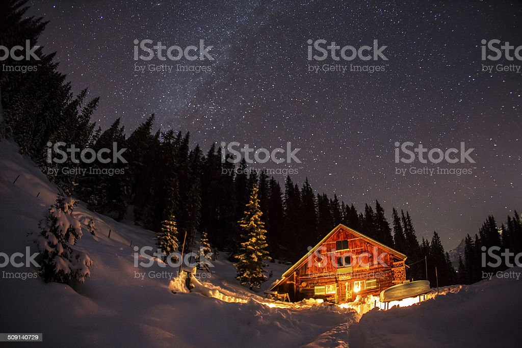 Lightened mountain hut in the austrian alps with milky way stock photo