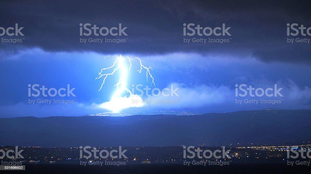 Lightening Striking Hills Above Town at Night stock photo