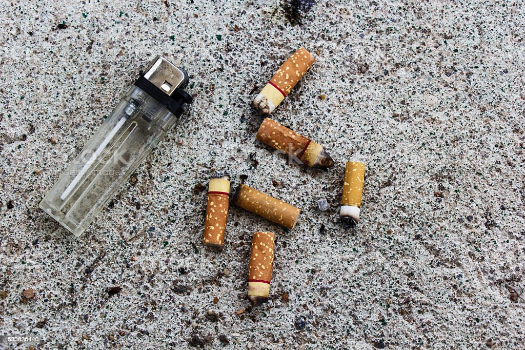 Lighter and cigarette butts on the ground. stock photo