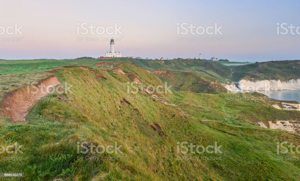 Lighthouse along rugged coastline at dawn. stock photo