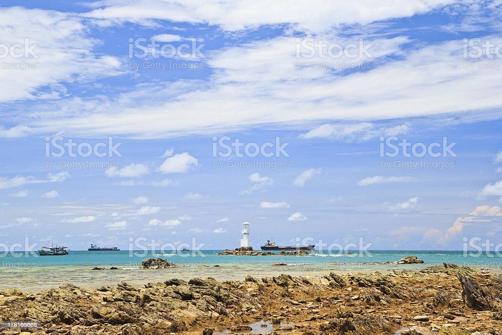 Lighthouse among blue sea, bluesky and submerged rocks royalty-free stock photo