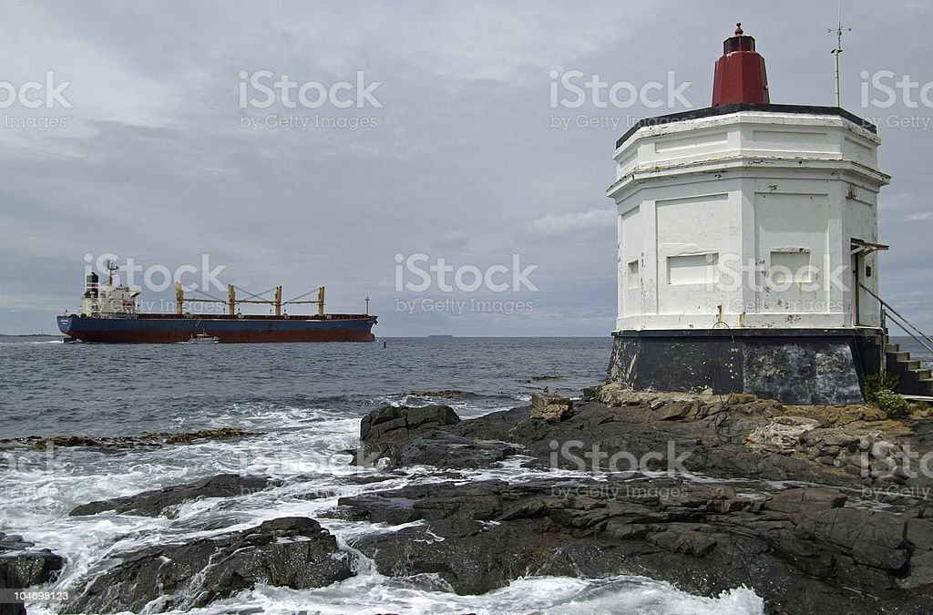 Lighthouse and container ship stock photo