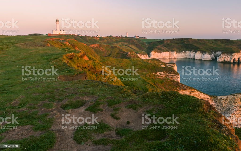 Lighthouse and erosion along rugged coastline and chalk cliffs at dawn. stock photo