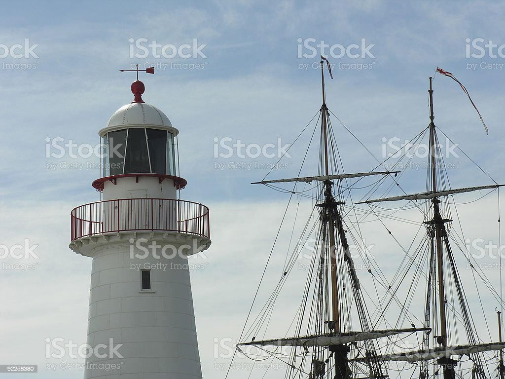 Lighthouse and sailing ship masts royalty-free stock photo